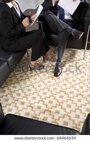 Cropped view of man and woman in business suits talking and reviewing report - stock photo