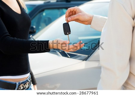 cropped view of man in car dealership giving car keys to client - stock photo