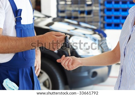 cropped view of mechanic giving car keys to female client - stock photo