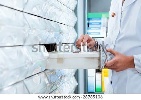 cropped view of pharmacist taking medicine from drawer. Copy space - stock photo