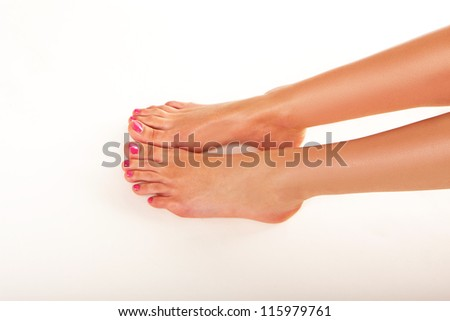 Cropped view of tanned bare female feet with manicured nails and red nail varnish - stock photo