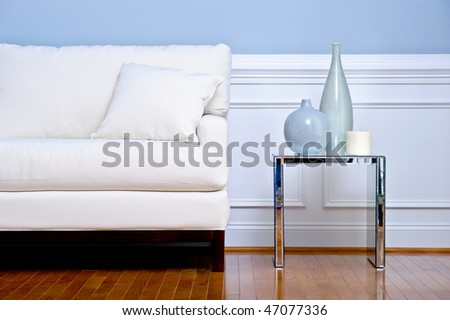 Cropped view of white couch and side table with vases, in a living room with a wood floor. Horizontal format.