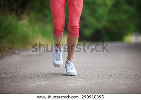 Cropped view of woman athlete running on pathway in park - stock photo