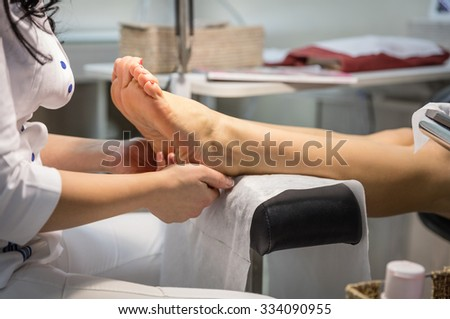 Cropped view of woman getting a pedicure and foot massage - stock photo