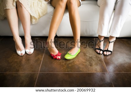 Cropped view of woman wearing mismatched shoes with women in high heels sitting beside - stock photo