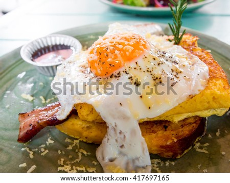 Croque madame delicious french breakfast with bacon, cheese, egg and sausage - stock photo