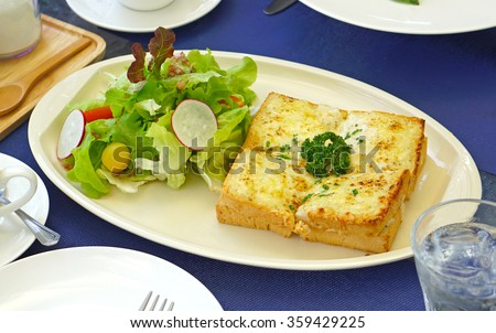Croque Monsieur, ham and cheese sandwich, with vegetable salad on blue table     - stock photo
