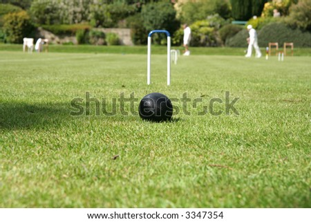 Croquet ball ready to be hit through the hoop - stock photo