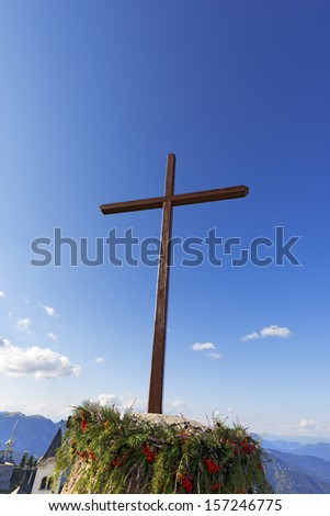 Cross Against the Blue Sky - Lussari Italy / Wooden cross with blue sky, pine branches and berries - Lussari Italy - stock photo