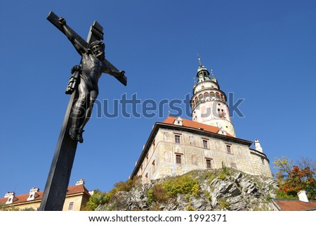 Cross and Baroque tower in Krumlov of Czech, the most beautiful town in the world - stock photo