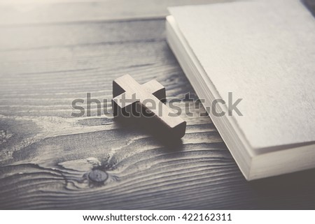 Cross and book on a wooden table