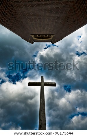 Cross and cathedral in a dramatic cloudy sky - stock photo