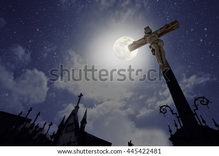 Cross and tombs in the form of chapels from an old european cemetery in a full moon night