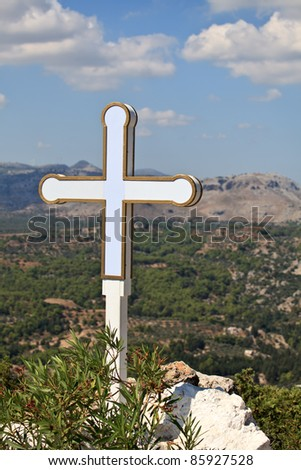 Cross at the peak of  Tsampika chapel. Rhodes. Greece.
