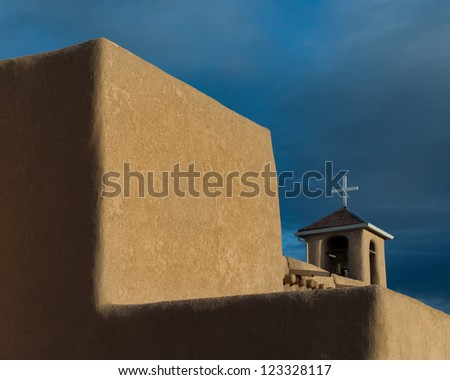 Cross behind large adobe walls of the San Francisco de Asis Mission Church in Ranchos de Taos