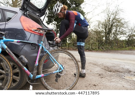 Cross-country cyclist by his car, changing after a bike ride - stock photo