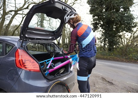 Cross-country cyclist taking bike out of the back of his car - stock photo