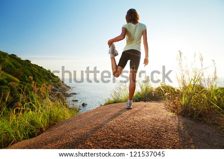 Cross country runner stretching on top of a hill and enjoying sunset sea view