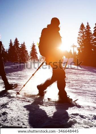 Cross country skier at sunrise or sunset moving through the snow with a sunburst over his shoulder - stock photo