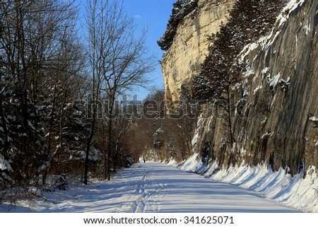 Cross-country skier skiing along a trail built by the bluffs of the Missouri River on a sunny day - stock photo