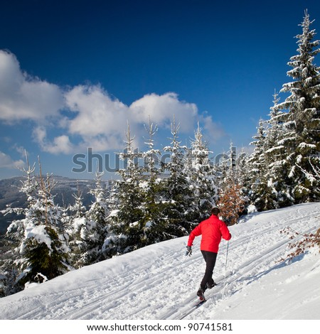Cross-country skiing: young man cross-country skiing on a lovely sunny winter day - stock photo