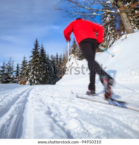 Cross-country skiing: young man cross-country skiing on a lovely sunny winter day (motion blur technique is used to convey movement) - stock photo