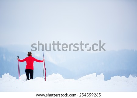 Cross-country skiing: young woman cross-country skiing on a  winter day (motion blurred image) - stock photo