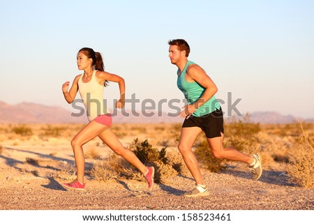 Cross-country trail running people at sunset. Runner couple exercising outside as part of healthy lifestyle. Multiracial runners couple, Asian woman, Caucasian man working out together. - stock photo