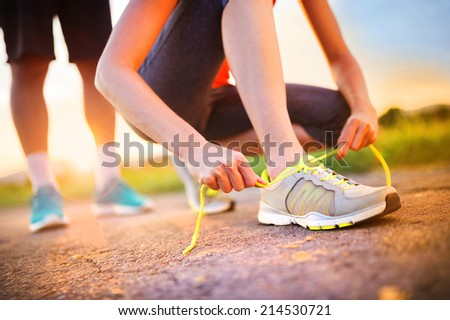 Cross-country trail running people at sunset. Runner couple exercising outside as part of healthy lifestyle. - stock photo