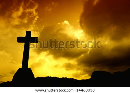 cross detail in silhouette and the clouds in the sky - stock photo