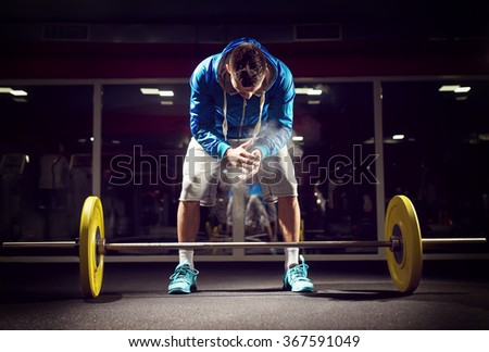 Cross fit weightlifter preparing for training. Shallow depth of field, selective focus on hands and dust. - stock photo