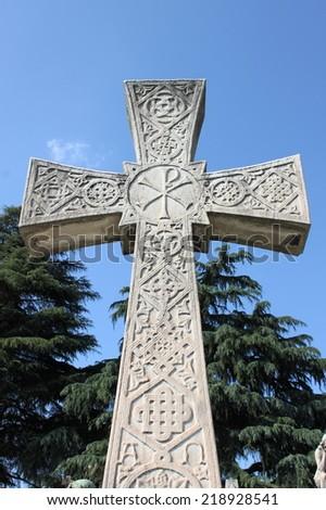 Cross gravestone in a graveyard - stock photo
