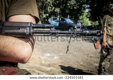 Cross hanging on a rifle of a soldier - stock photo
