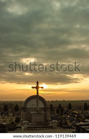Cross in a cemetery in the light of sunset in Provins, France - stock photo