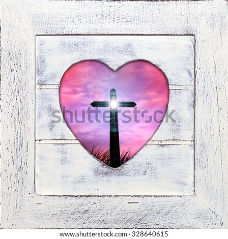 cross in a grass, sunset sky ,wooden frame with heart shape - stock photo
