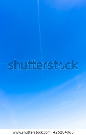 cross in the blue sky created by  contrails