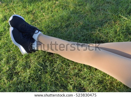 Cross legs in legging belongs to beautiful girl lay on green grass.
