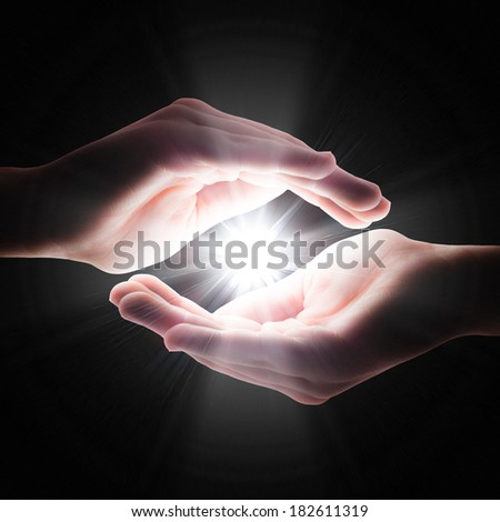 cross light in the darkness in your hands - stock photo