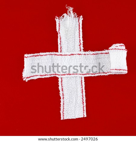 cross made of white bandages on a red chalk background - stock photo
