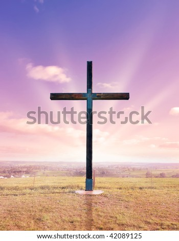 cross of christ in field at sunset or sunrise