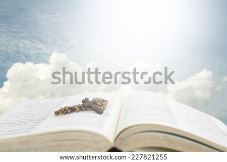 Cross of rosary beads resting against open bible with sky background. - stock photo