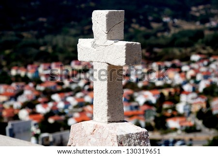 Cross on a hill over a small city Baska, Croatia - stock photo