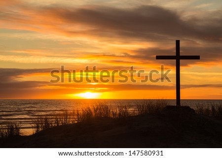 Cross on a sand dune with a wonderful setting sun in the background. - stock photo