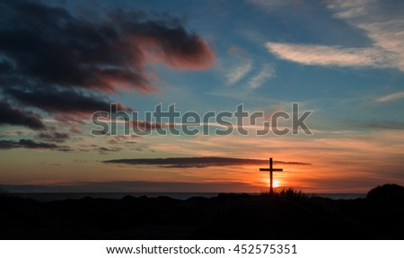 Cross on a sand dune with a wonderful sunset sky in the background