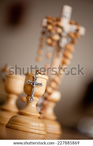 Cross on candle holder and blurred rosary made of wood beads dangle on wooden cross, vertical orientation, nobody.