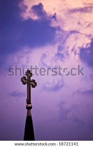 cross on cloudy purple sky