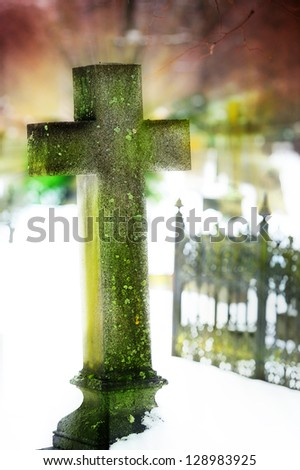 Cross on graveyard. Intentional high key background. - stock photo