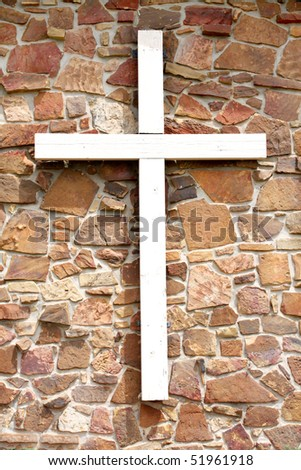 Cross on rock wall - stock photo