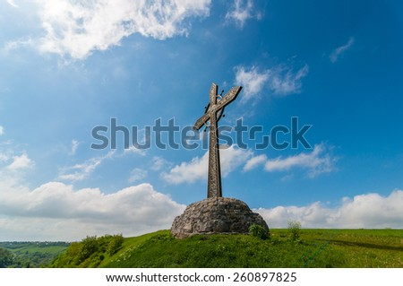 Cross on the mountain on a background of blue sky and clouds. Easter, spring - stock photo