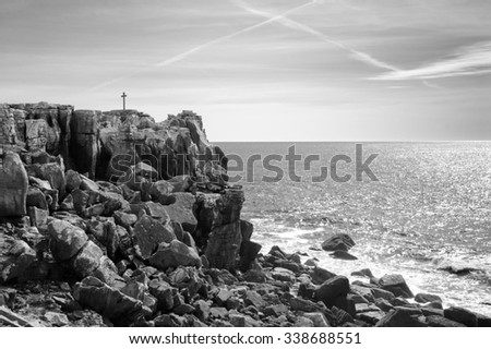 Cross on the rocky summit over the ocean. Cross in the sky - plane trace. Peniche, Portugal. Aged photo. Black and white. - stock photo